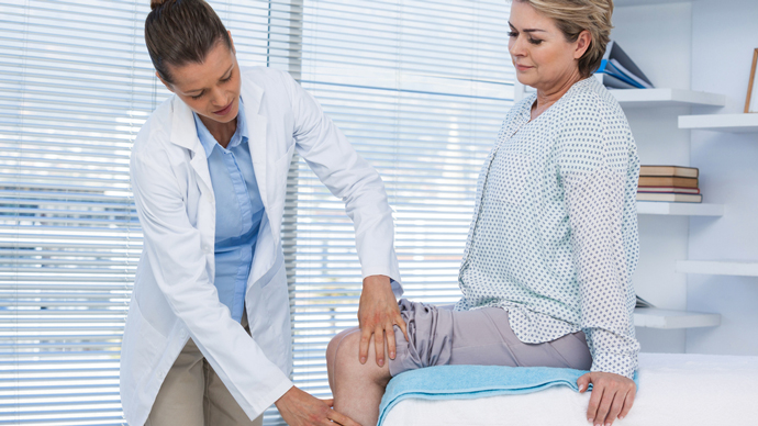 a doctor examines a woman's knee in a doctor's office