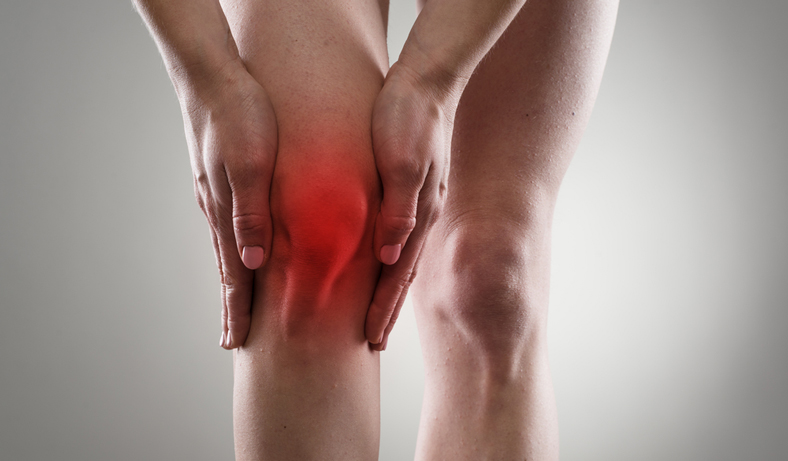 woman holds her knee in pain