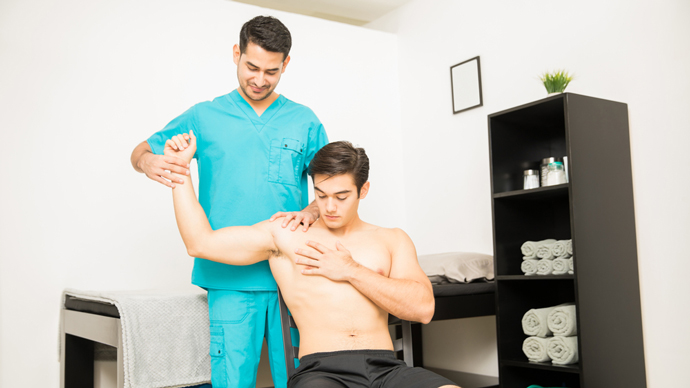 doctor examines man with shoulder pain